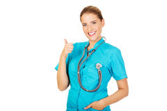 Young female doctor or nurse with stethocope shows thumb up Stock Photography