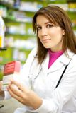 Young female doctor in pharmacy smiling Royalty Free Stock Photos