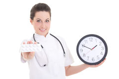 Young female doctor with pills and clock isolated on white Stock Image
