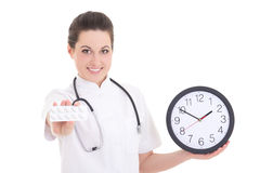 Young female doctor with pills and clock over white Royalty Free Stock Images