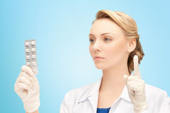 Young female doctor with pills pointing finger up Royalty Free Stock Photos