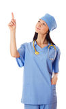 Young female doctor pointing finger upwards. Isolated on white background Royalty Free Stock Photo