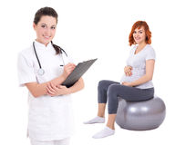 Young female doctor with pregnant woman sitting on fitness ball. Young female doctor with pregnant women sitting on fitness ball isolated on white background Royalty Free Stock Images