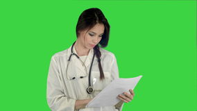 Young female doctor reading patient medical history forms on a Green Screen, Chroma Key. Young female doctor reading patient medical history forms. Professional stock video footage