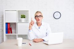 Female doctor or scientist showing idea sign in office Stock Photo