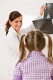 Young female doctor show x-ray to child Royalty Free Stock Photos