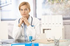 Young female doctor sitting at desk Royalty Free Stock Photos