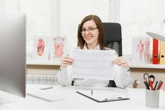 Young female doctor sitting at desk with medical documents, electrocardiogram record, heart ekg cardiogram chart of wave. In paper in light office in hospital stock images