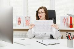 Young female doctor sitting at desk with medical documents, electrocardiogram record, heart ekg cardiogram chart of wave. In paper in light office in hospital royalty free stock photos