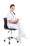 Young female doctor sitting over white background Royalty Free Stock Photos