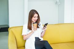 Young Female doctor sitting on yellow sofa in medical centre with mobile phone and drinking coffee during her break. Student on. Practice. Copy space royalty free stock images