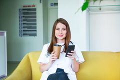 Young Female doctor sitting on yellow sofa in medical centre with mobile phone and drinking coffee during her break. Student on. Practice. Copy space royalty free stock photo