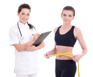 Young female doctor and sporty woman with measure tape isolated Royalty Free Stock Photos
