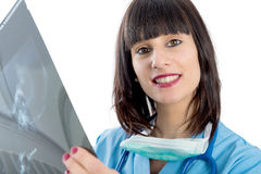 Young female doctor with stethoscope looking at patients x-ray Royalty Free Stock Photography