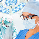 Young female doctor with surgeon on background Stock Photos