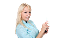 Young female doctor with a syringe. And cell phone in a hand.isolated over white Royalty Free Stock Photo