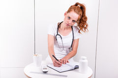 Young female doctor is taking notes during a consultation Stock Images
