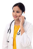Young female doctor talking on mobile phone Royalty Free Stock Photography