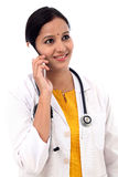 Young female doctor talking on mobile phone Stock Image
