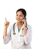 Young female doctor talking on mobile phone Stock Photography