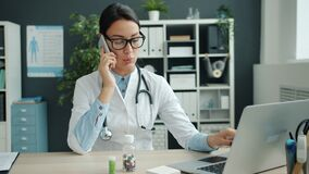 Young female doctor talking on mobile phone and using laptop working in office