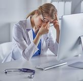 Young female doctor tired after working with computer stock photos