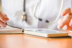 Young female doctor using modern smartphone in the hospital, seeking information in the internet. Close up stock photography