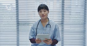 Young female doctor using tablet and talking to camera 4k stock video footage