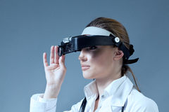 Young female doctor wearing magnifying glass equip Royalty Free Stock Image