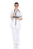 Young female doctor wirting in a book. Royalty Free Stock Photography