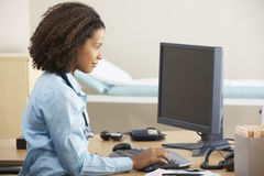 Young female Doctor working on computer at desk Stock Photo