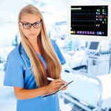 Young female doctor writing prescription in ICU Royalty Free Stock Image