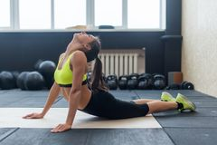 Young female doing back stretching exercise, fit woman warming-up in gym stock image