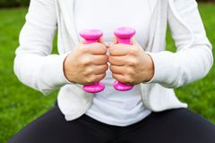 Fitness routine in the park. Young female doing fitness exercises with pink dumbbells in the park, green grass Stock Photo