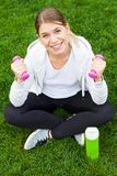 Fitness routine in the park. Young female doing fitness exercises with pink dumbbells in the park, green grass Stock Images