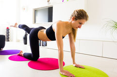 Young female doing her leg raise exercise in her home. Royalty Free Stock Images
