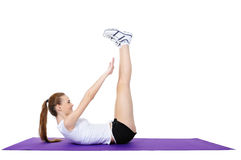 Young female doing physical exercises on the floor stock images