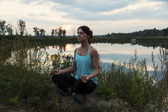 Young female doing yoga by the lake Stock Image