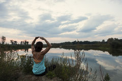Young female doing yoga by the lake Stock Images