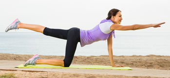 Young female doing yoga poses  on sunny beach Royalty Free Stock Photo