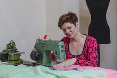 Young female dressmaker choosing material from catalogue in studio. Royalty Free Stock Photography