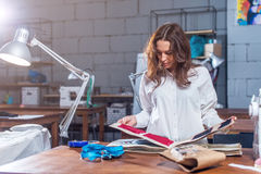 Young female dressmaker choosing material from catalogue in studio. Tailor looking through fabrics while standing in a Royalty Free Stock Photo
