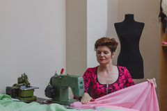 Young female dressmaker choosing material from catalogue in studio. Stock Photo
