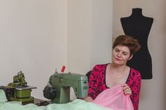 Young female dressmaker choosing material from catalogue in studio. Royalty Free Stock Image