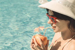 Young female drinking grapefruit juice next to the swimming pool Royalty Free Stock Photo
