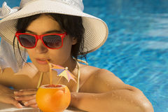 Young female drinking grapefruit juice in the swimming pool Stock Photography