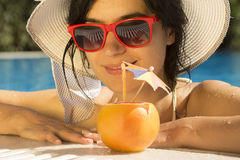 Young female drinking grapefruit juice in the swimming pool Stock Images