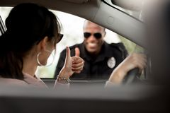 Young female driver in car and smiling policeman. Doing thumb up gesture to each other royalty free stock photography