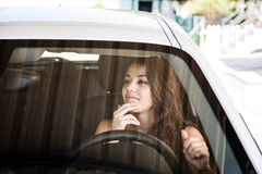 Young female driver checking appearance in car mirror Royalty Free Stock Images