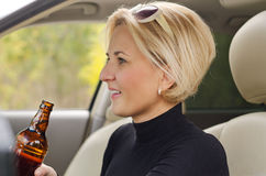 Young female driver drinking alcohol in the car Royalty Free Stock Photography